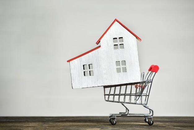 Casa modelo e carrinho de compras. comprando o conceito de casa. aluguel de hipoteca.