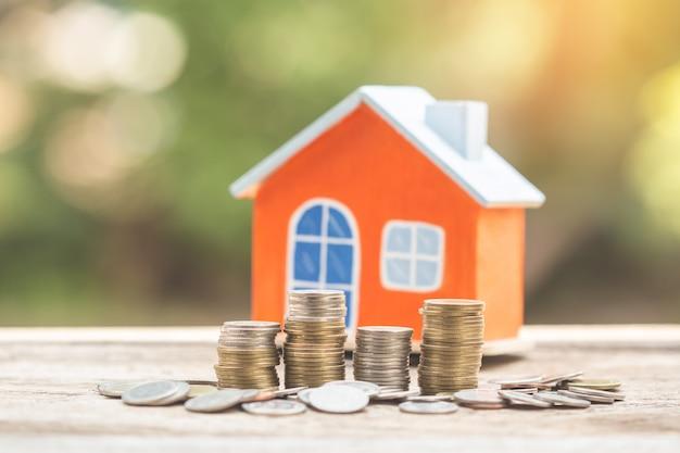 Casa modelo e moeda dinheiro, hipoteca e investimento imobiliário.