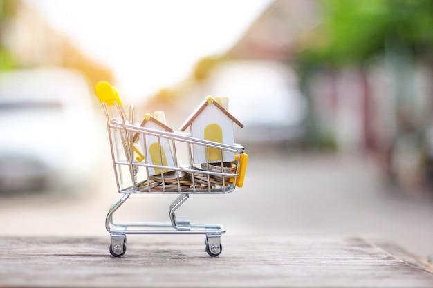 Casa modelo e moeda no conceito de carrinho de compras para poupança de hipoteca