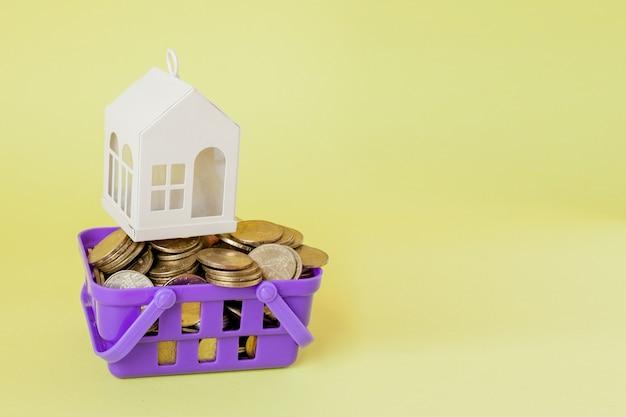 Casa modelo e moeda no conceito de cesto de compras para economia de hipoteca em fundo amarelo.