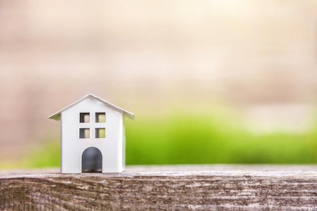 Casa modelo em miniatura de brinquedo branco em fundo de madeira