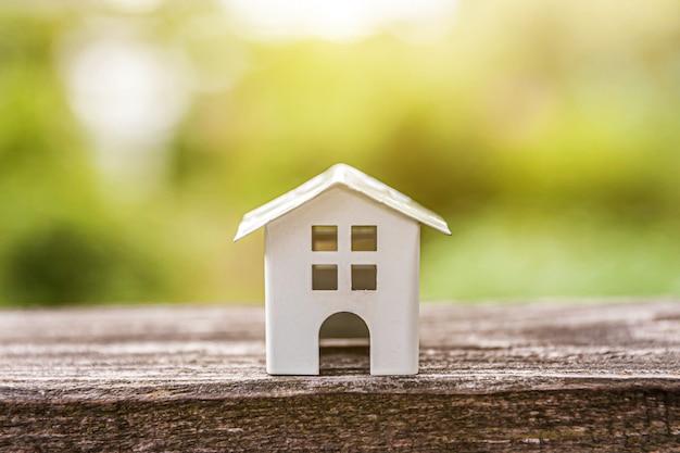 Casa modelo em miniatura de brinquedo branco em madeira perto de pano de fundo verde