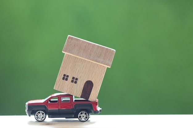 Casa modelo em modelo de carro em miniatura no fundo verde da natureza, investimento e conceito de negócios