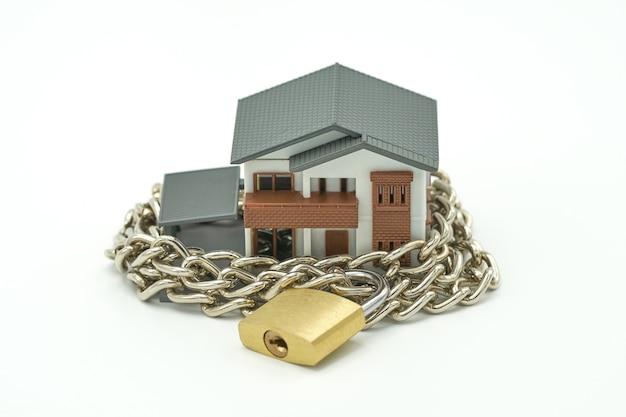 Casa modelo envolvida com corrente de aço e cadeado. segurança de idéias.