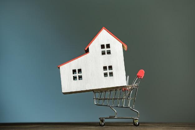 Casa modelo no carrinho de compras. compre o conceito de casa. fundo escuro, vista frontal.