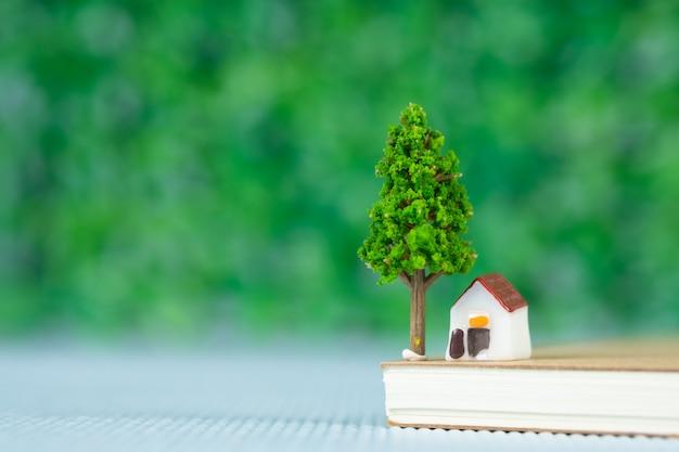Casa modelo pequena e pequena árvore com notebook, banco de poupança