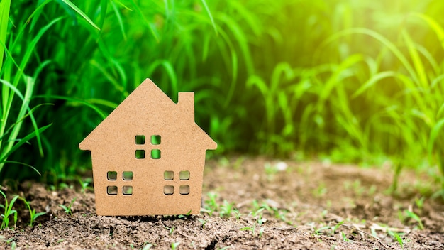 Casa modelo pequena no campo de grama verde.