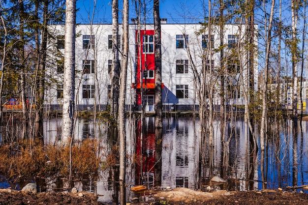 Casa moderna e uma grande poça perto dela, área inundada