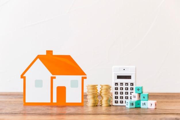 Casa, moedas empilhadas, calculadora e blocos de matemática na superfície de madeira