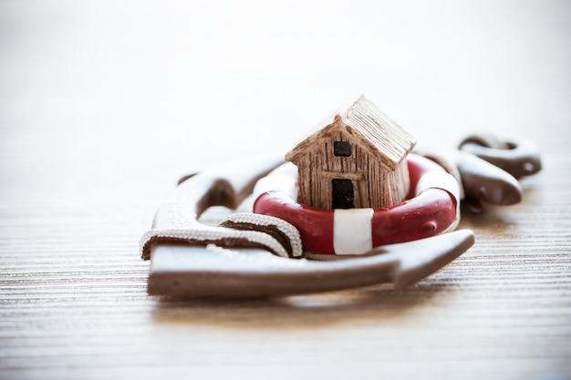 Casa na âncora de lifebuoy vermelho na madeira