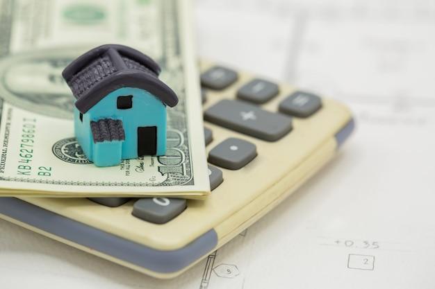 Casa na calculadora com notas de dólar