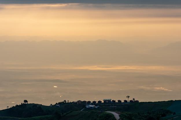 Casa na colina e manhã névoa coberta de montanhas.