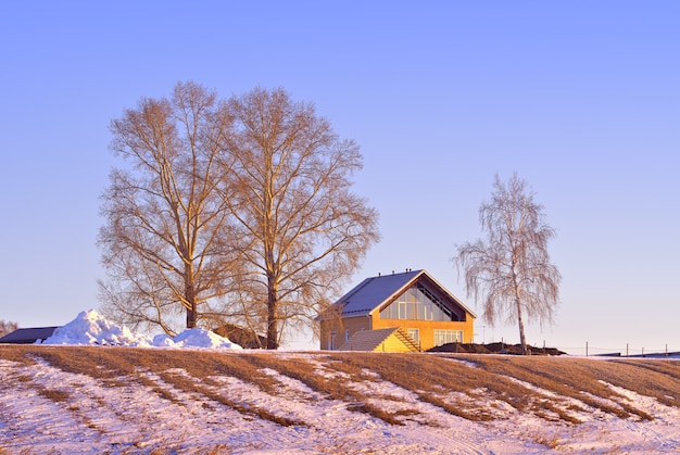 Casa na costa de inverno do mar ob a encosta da praia com árvores nuas