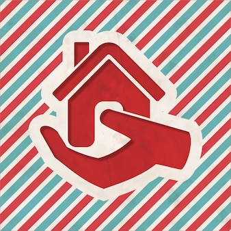 Casa na mão ícone sobre fundo listrado de vermelho e azul. conceito vintage em design plano.