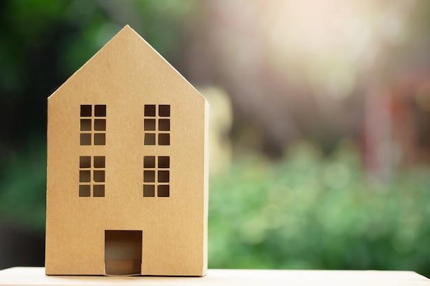 Casa no modelo de papel reciclado marrom definir muitas costas na mesa de madeira no fundo de luz solar do jardim da manhã.