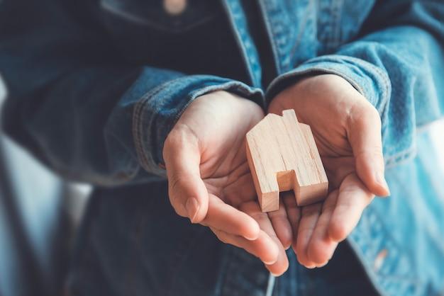 Casa nova e conceito da propriedade imobiliária, mulher que guarda a casa modelo de madeira nas mãos.
