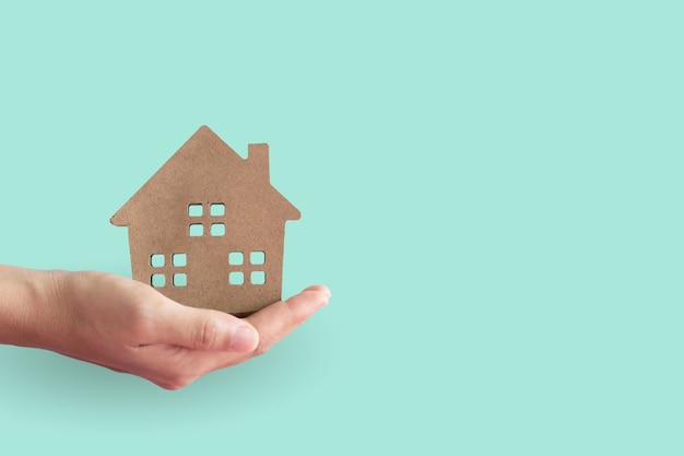 Casa ou modelo de casa na mão da mulher na sala de cor pastel.