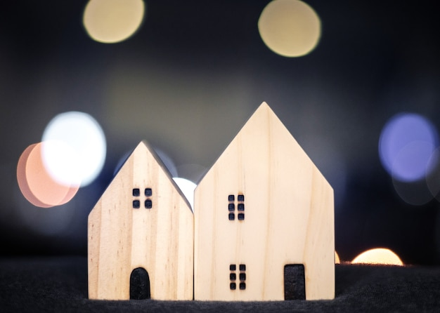 Casa ou modelo de madeira para casa para o conceito de família feliz com luz bokeh do centro moderno da cidade
