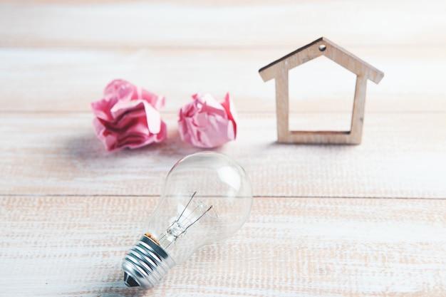 Casa, papel amassado e uma lâmpada em cima da mesa