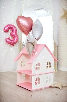 Casa para brincar com bonecas com um telhado rosa fica no chão em uma sala iluminada, decorada com balões com hélio