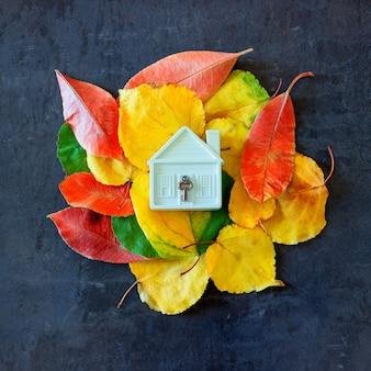 Casa pequena do brinquedo entre as folhas de outono coloridas.