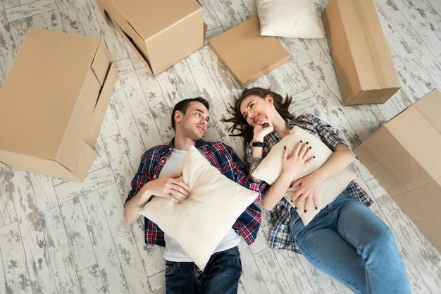 Casa, pessoas, reparação e conceito imobiliário - casal feliz com caixas de papelão e outras coisas, deitado no chão para o novo lugar