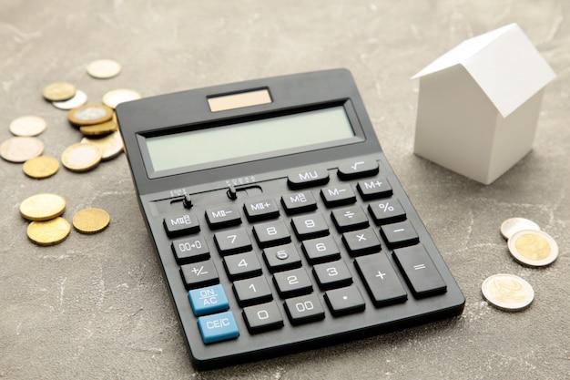 Casa que descansa no conceito da calculadora para a calculadora da hipoteca, as finanças domésticas ou a economia para uma casa.