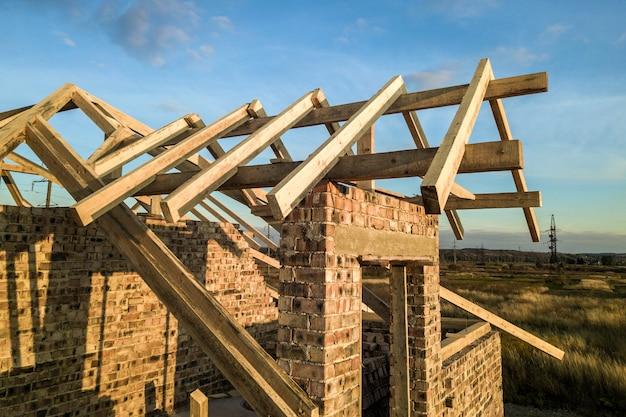 Casa residencial privada com estrutura de estrutura de telhado de madeira em construção. edifício de tijolo inacabado em desenvolvimento.