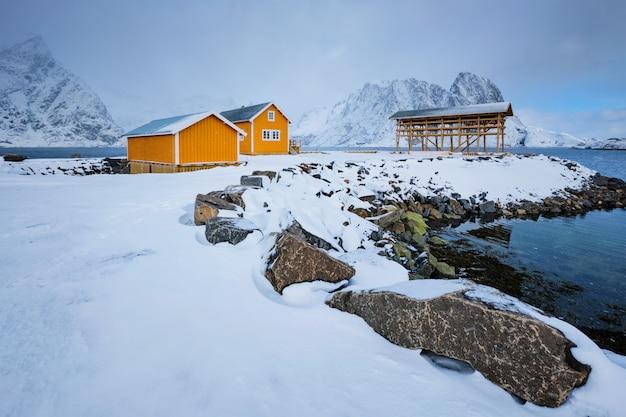 Casa rorbu e flocos de secagem para bacalhau no inverno. ilhas lofoten, noruega