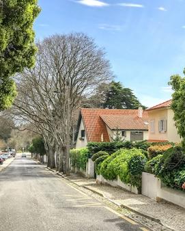Casa rural amarela com telhado de telha laranja e jardim com árvore na cidade de cascais, portugal