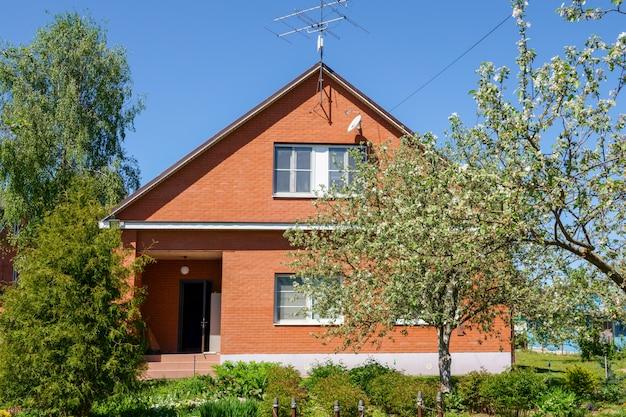Casa russa vermelha com telhado de metal e cerca de metal