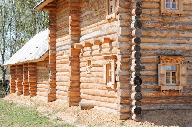 Casa rústica de madeira feita de madeira e janelas com persianas esculpidas no antigo estilo rural russo. construção de casas feitas de materiais ecológicos naturais