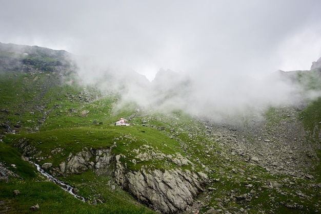 Casa solitária isolada em um belo prado rochoso verde