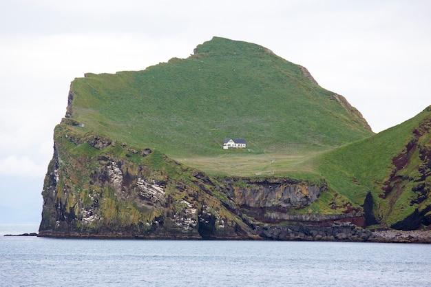 Casa solitária na ilha do arquipélago vestmannaeyjar. islândia