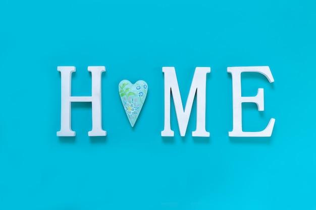 Casa, texto de madeira com uma decoração de forma de coração em fundo azul. conceito de construção de casas, escolha de sua própria casa, hipoteca, compra, venda de área residencial, aluguel, seguro, investimento imobiliário.
