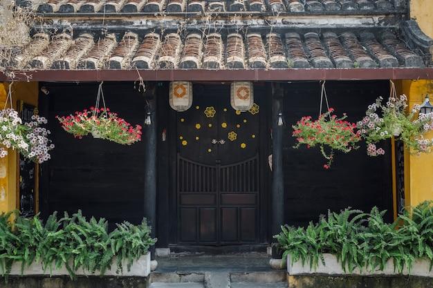 Casa tradicional com portas marrons e lanternas chinesas em hoi, uma cidade velha. patrimônio mundial. vietnã