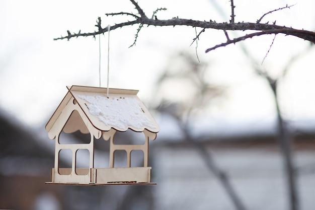 Casa vazia de brinquedo de madeira pendurada na árvore no inverno.