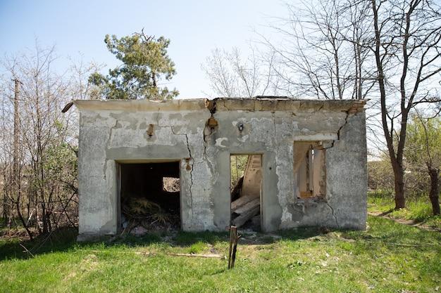 Casa velha em ruínas abandonada. ao redor da casa cresceram árvores.