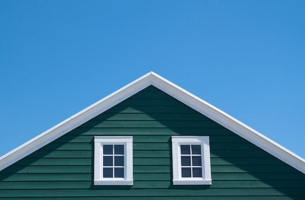 Casa verde e telhado branco com céu azul no dia ensolarado