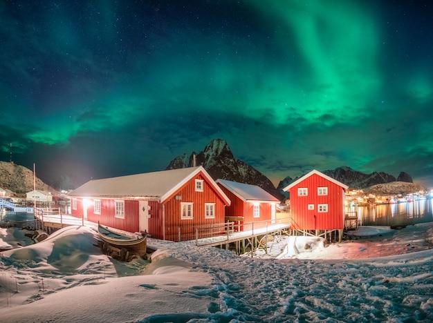 Casa vermelha na vila de pescadores com aurora boreal sobre o oceano ártico no inverno à noite