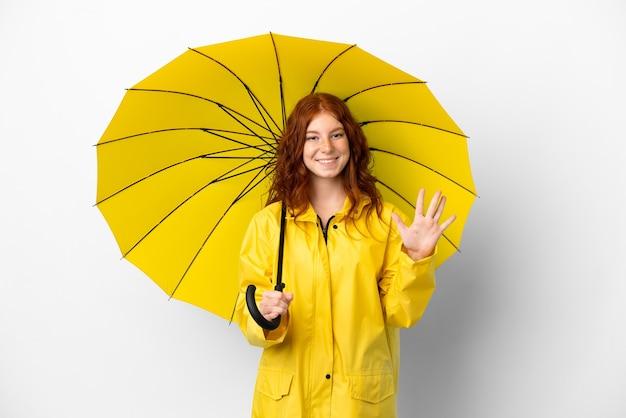 Casaco à prova de chuva e guarda-chuva da menina ruiva adolescente isolado no fundo branco contando cinco com os dedos