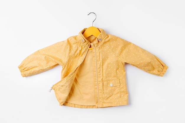 Casaco amarelo pendurado cabide em fundo branco. roupa de outono bonito de crianças.