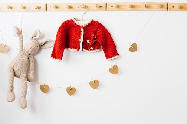 Casaco de bebê e brinquedo de pelúcia