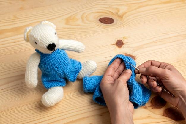 Casaco de brinquedo de tricô com mãos em close