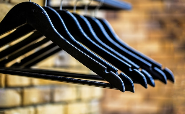Casaco de cabides em madeira. muitos cabides pretos de madeira em uma haste. conceito de loja, venda, design, cabides vazios.