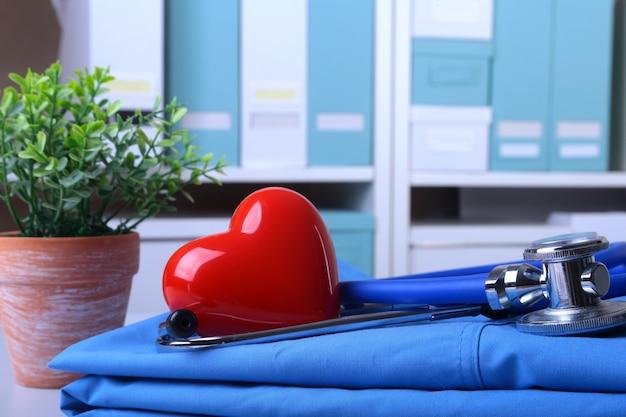 Casaco de médico com estetoscópio médico e coração vermelho em cima da mesa