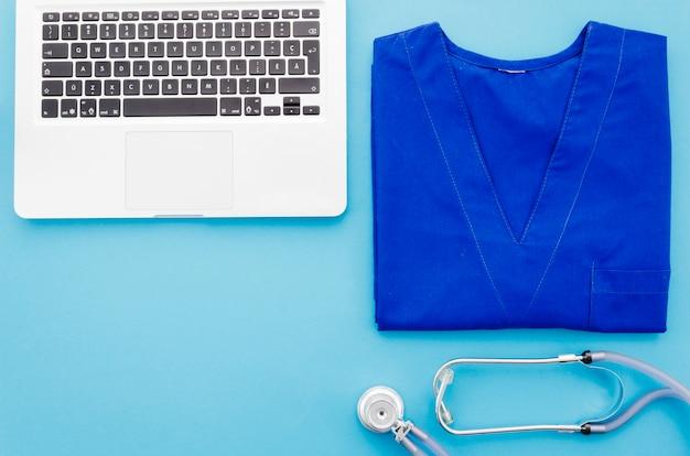 Casaco médico azul; estetoscópio e laptop em fundo azul