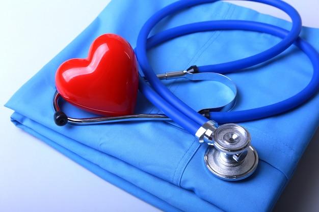 Casaco médico com estetoscópio médico e coração vermelho na mesa