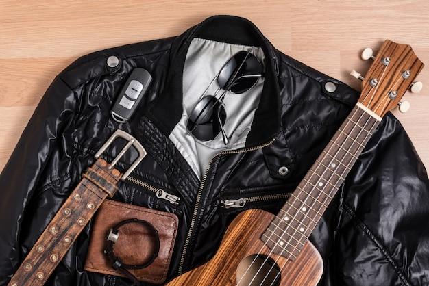Casaco preto com acessórios masculinos e ukulele