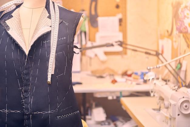 Casaco semi-pronto em manequim com fita métrica no pescoço. confecção de terno em processo de jaqueta sob medida. confecção de terno sob medida em oficina de alfaiataria. trabalhando em um paletó feito sob medida
